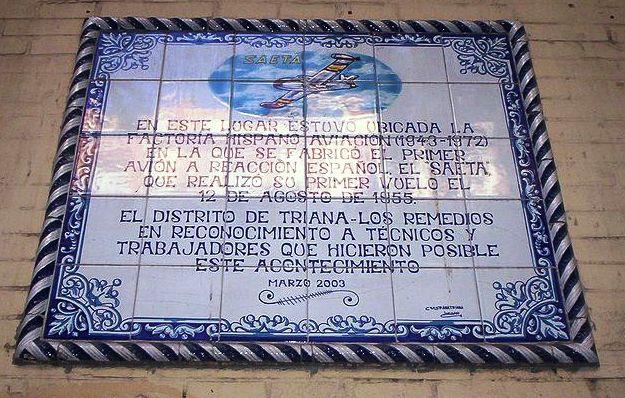 Este retablo cerámico colocado en la fachada de la antigua fábrica de la Hispano Aviación en Sevilla recuerda la histórica efeméride del primer vuelo del Saeta y el orgullo de la ciudad por albergar su génesis y desarrollo (Fuente: sevilladailyphoto.blogspot.com)