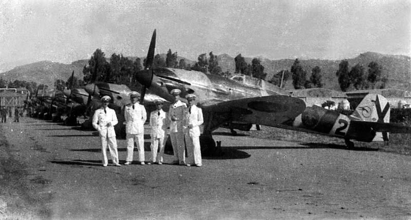 Pilotos españoles posan con su uniforme de gala ante la línea de vuelo de He 112B en la base aérea de Tauima un 18 de julio de 1944. Los aviones aún conservan las escarapelas del yugo y las flechas (Fuente: J. Pizarro/Gonzalo Ávila/manupedia.com)