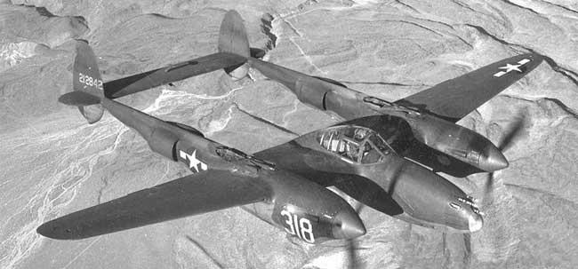 Lockheed P-38 Lightning en vuelo. Este revolucionario caza pesado de interceptación bimotor tenía doble fuselaje y era capaz de cumplir múltimples funciones. La versión F tenía afustes subalares para transportar bombas o depósitos de combustible auxiliares