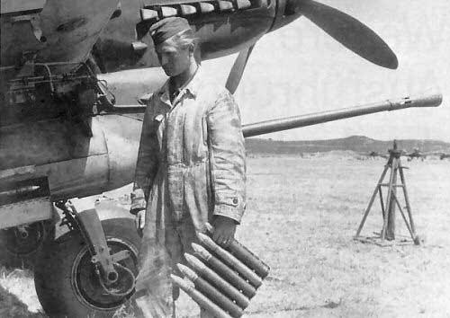 Un mecánico se prepara para alimentar uno de los cañones BK 37 de un Stuka con el peine de seis proyectiles con cabeza de wolframio que lleva en la mano