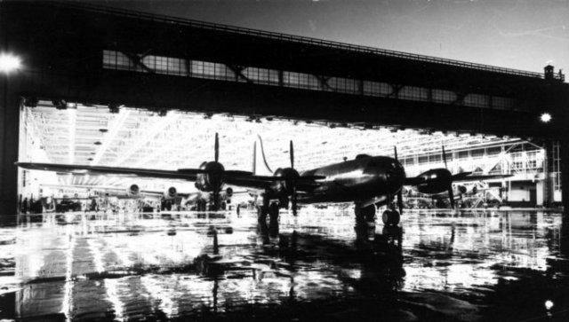 Una superfortaleza emerge de la gran factoría de Wichita en una lluviosa noche en Kansas. Esta fábrica proporcionó los primeros aviones de la primera ala de combate de B-29