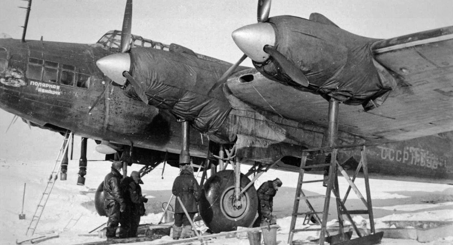 Personal de tierra trabaja en un gélido aeródromo ártico. El ejemplar va propulsado por los radiales Shvetsov M-82 (ASh-82), aquí cubiertos por lonas térmicas para el funcionamiento del sistema de bombeo de aire caliente. Las matrículas civiles permiten aventurar que se trata de una unidad de posguerra