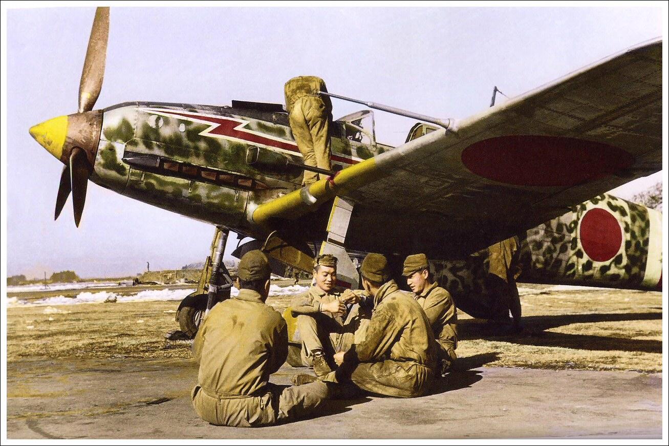 Magnífica imagen coloreada de un Ki-61 en tierra mientras varias tripulaciones disfrutan de un momento de descanso. Obsérvese la exuberante y colorista decoración moteada del camuflaje del avión