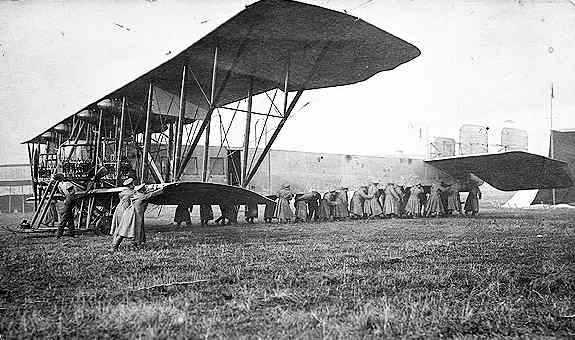 Tropas de tierra ayudan a trasladar el gran cuatrimotor a la cabecera de pista antes de una misión de bombardeo
