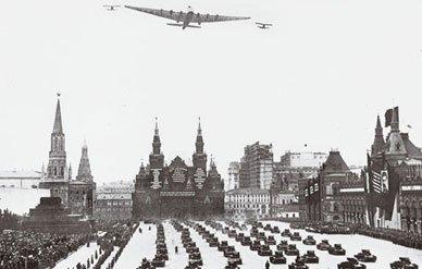 El gigantesco ANT-20, escoltado por dos cazas I-5, sobrevuela la Plaza Roja durante un desfile militar el 19 de julio de 1934 (fuente: Von Hardesty/NASM)