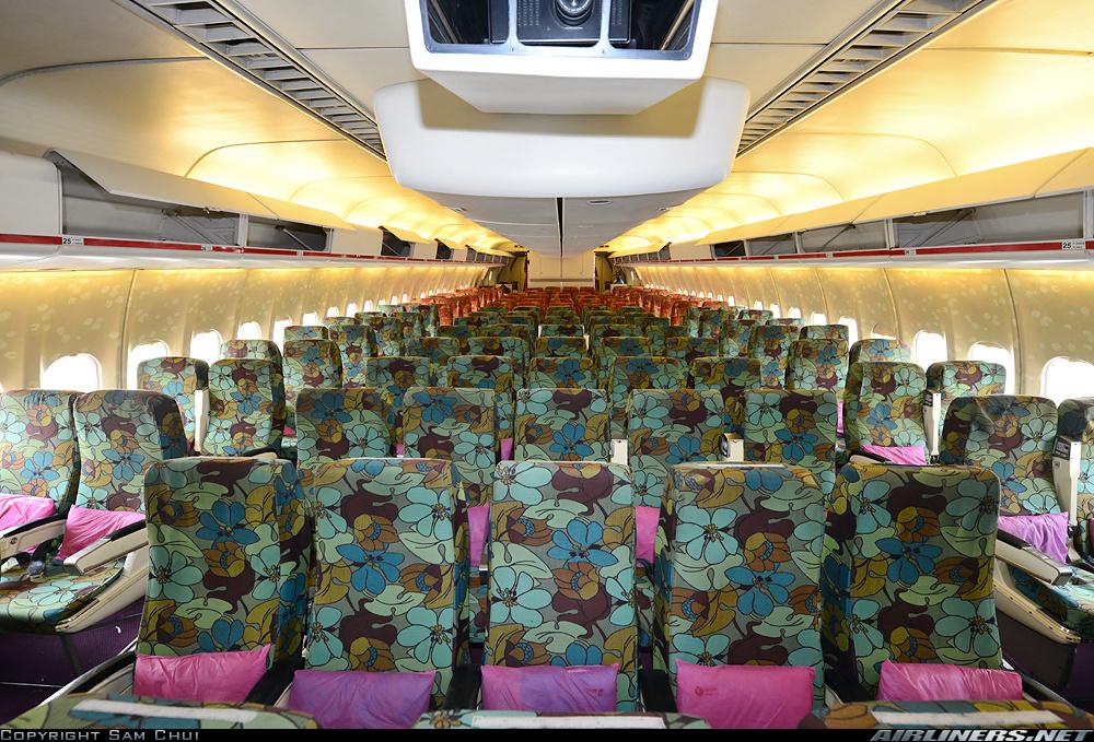 También se nota el paso de los años en esta colorista cabina de pasajeros, con proyector de pantalla gigante, tapizados retro y configuración 2-5-2. El avión estaba configurado para 314 pasajeros, todos en una sola clase. (fuente: Sam Chui / Airliners.net)