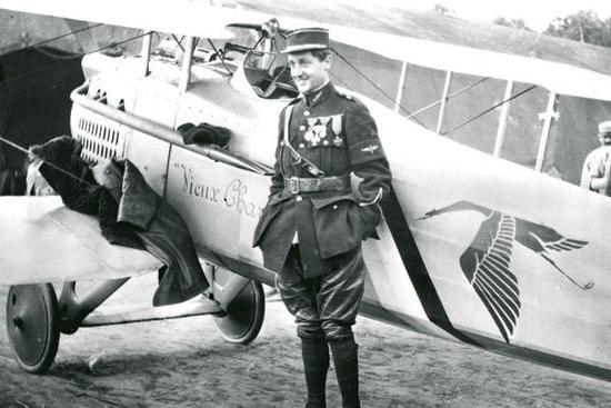 """El as Charles Guynemer posa ante su archifamoso SPAD S.VII """"Vieux Charles"""" de la escuadrilla SPA 3, """"Les Cicognes"""". El emblema de la unidad fue empleado desde entonces por la propia compañía en sus lujosos automóviles"""