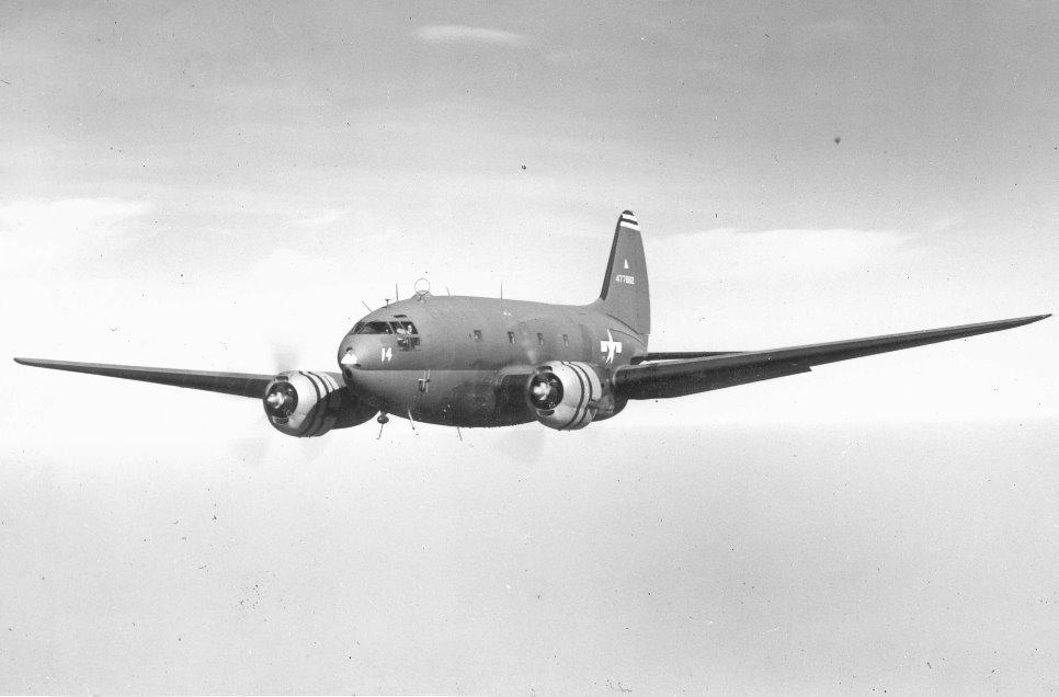 Un Curtiss C-46 Commando, concretamente un C-46D en vuelo. Este ejemplar, asignado al 302nd Air Transport Wing, fue de los escasos Commandos que volaron en Europa durante la Segunda Guerra Mundial.(www.stinsonflyer.com)