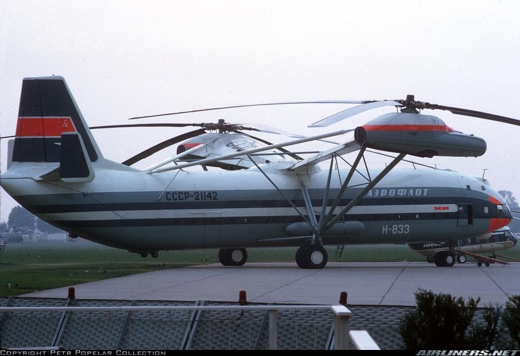 El enorme Mil Mi-12 en el Salón parisino de Le Bourget de 1971. Obsérvese el enorme tren triciclo y las formas del portalón de popa. Los dos tanques cilíndricos a los costados albergaban el combustible. El helicóptero que aparece detrás es un Mil Mi-8, sirviendo para hacer una comparativa de su desmesurado tamaño (Petr Popelar Collection / Airliners.net)