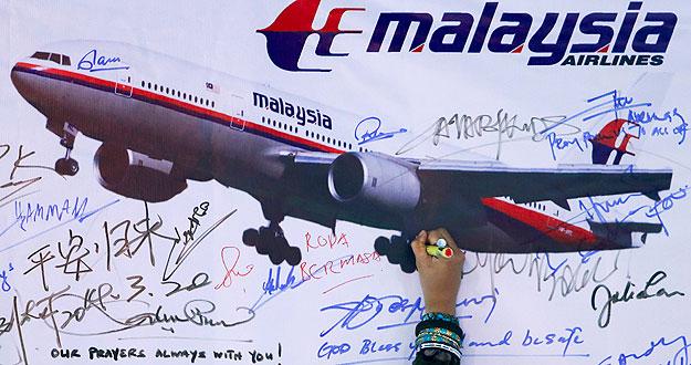 Un mujer escribe un mensaje en recuerdo del vuelo MH370 de Malaysia Airlines (REUTERS/Samsul Said)