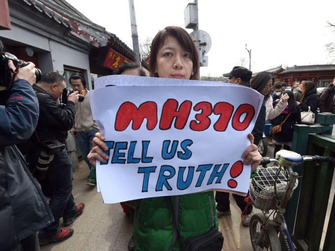 Un familiar de uno de los pasajeros chinos desaparecidos en el vuelo MH370 sujeta una pancarta (El Mundo / AFP)