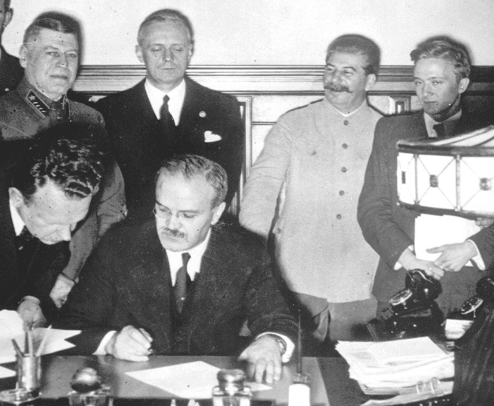 En esta foto tomada el 23 de agosto 1939, el dictador soviético Josef Stalin, se muestra sonriente mientras su Ministro de Asuntos Exteriores, Vyacheslav Molotov, sentado, firma el Pacto de No Agresión con su contraparte del Reich, Joachim von Ribbentrop, de pie a la derecha de Stalin, en Moscú. El hombre situado a su derecha es el Ministro de Defensa y jefe de Estado Mayor del Ejército Soviético, el Mariscal Boris Shaposhnikov. En este Tratado, existía una cláusula secreta firmada, por la que ambos Regímenes dividían Europa en grandes áreas de influencia, y que, por ejemplo, permitieron a Alemania invadir cómodamente Polonia pocos días más tarde. (AP Photo/File)