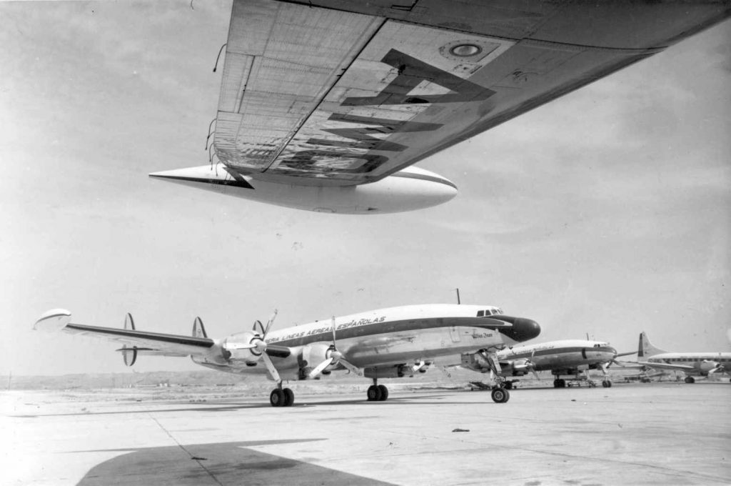 """Espectacular foto de varios magníficos ejemplares de la Flota Iberia de finales de los cincuenta y principios de los sesenta. Bajo la sombra del L-1049 se puede ver, de izquierda a derecha, al L-1049H """"San Juan"""", un L-1049C no identificado y un bimotor Convair 240 (http://www.puentedemando.com)."""