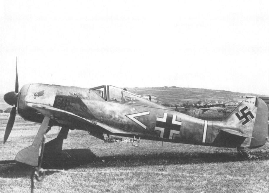 """Humillado, el Fw 190A-3 del Oberleutnant Faber permanece estacionado en el aeródromo galés de Pembrey. Obsérvese la cabeza de gallo pintado en el capó, insignia del Gruppenkommandeur del III/JG 2, el Hauptmann (capitán) Hans Hahn. En alemán, """"Hahn"""" significa literalmente gallo."""