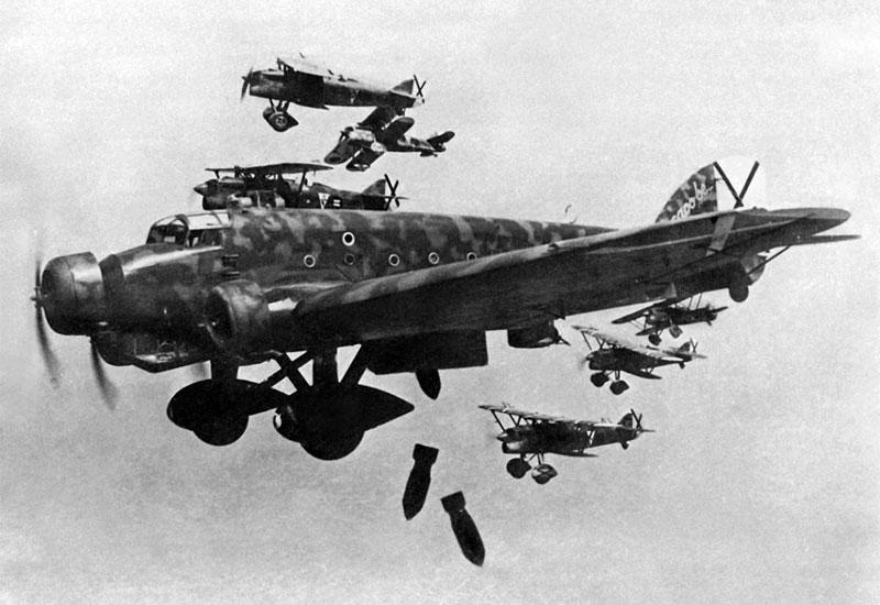 """El SM.81 21-44 (identificable por la palabras """"capo be..."""", o """"Sea el jefe..."""" en la deriva), lanza bombas de 50 kg en una misión de bombardeo, escoltado por cazas Fiat CR-32 del XVI Grupo de caza. Ésta y otras muchas fotos fueron tomadas por Rino Zitelli, piloto de la Aviazione Legionaria."""