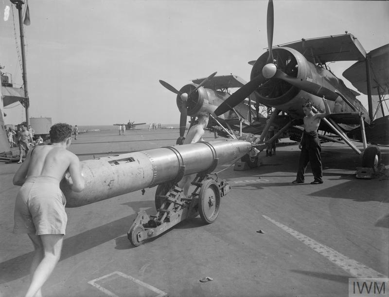 Armeros sitúan un torpedo de instrucción bajo un Fairey Swordfish, a bordo del HMS Illustrious, en octubre de 1942. (© IWM. Original Source: http://www.iwm.org.uk/collections/item/object/205146243)
