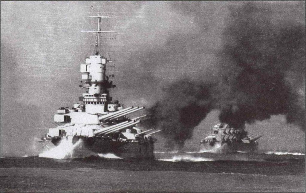 Los acorazados Vittorio Veneto y Littorio navegando en formación y abriendo fuego por babor con sus poderosas piezas de 381 mm, en una misión de escolta de convoyes a principios de la guerra