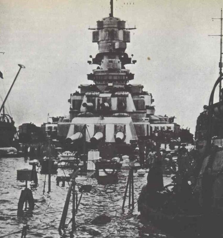 El poderoso acorazado Littorio, con el agua a la altura de la cubierta de proa, yace, tras encajar tres impactos de torpedo, con la quilla en el fondo de la rada. Las reparaciones le mantuvieron cuatro meses fuera de servicio (http://www.armouredcarriers.com).