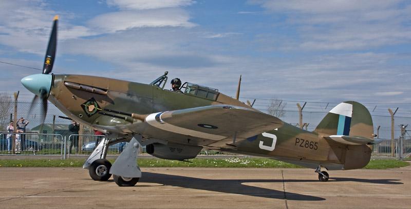 El Hurricane PZ865 carretea en la base de la RAF en Coningsby, hogar del Battle of Britain Memory Flight, con el esquema de colores actual, perteneciente al South East Asia Command, 34 Squadron y con las bocachas de sus cuatro cañones Hispano recuperadas (www.memorialflightclub.com).