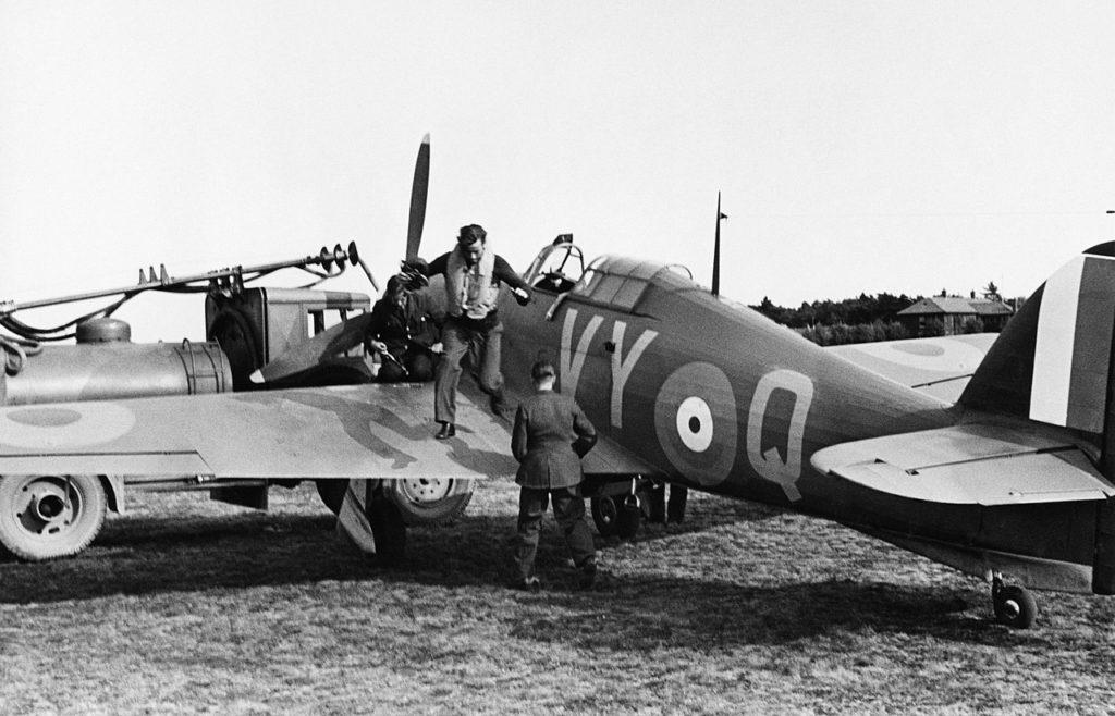 """El Capitán y Lider del Escuadrón nº 85 de la RAF, Peter Townsend, desciende de su Hawker Hurricane Mk.I P3854 """"VY-Q"""", mientras personal de tierra procede a repostar el avión, en la base de Castle Camps, en Cambridgeshire, en plena Batalla de Inglaterra. Townsend mantuvo tras la guerra una larga relación amorosa con la Princesa Margarita, hija menor del rey Jorge VI que hizo correr ríos de tinta en los tabloides sensacionalistas de la época (https://www.iwm.org.uk/)."""
